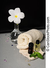 Spa essentials - Essential oils and towels and frangipani...