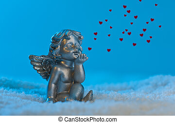 Angel in a beautiful blue snow setting, shows heart