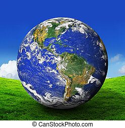 earth - blue planet Earth on green grass and blue sky...