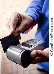 African man's hand, swiping a credit card through a wireless...