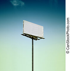 Blank billboard in the middle of nowhere agains blue moody...