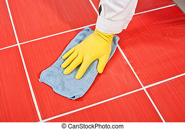 Worker with yellow gloves and blue towel clean red tiles...