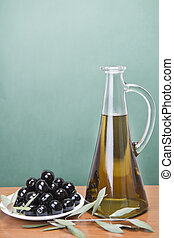 Olive oil and a plate with black olives.
