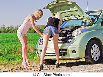 Two blonde girls standing by the broken car and trying to...