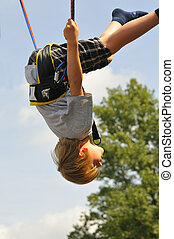 Fun - Blond boy jumping on the trampoline  bungee jumping