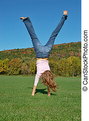 Handstand - Girl doing a handstand in green field