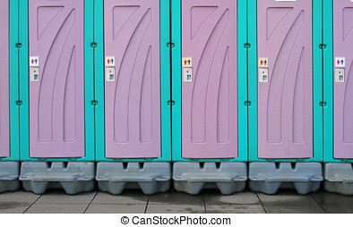 Temporary Toilets - -- a row of portable toilets set up at a...