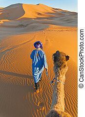 Berber walking with camel at Erg Chebbi, Morocco - Berber...