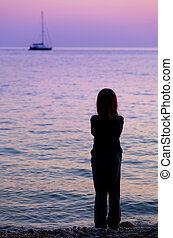 silhouette of a girl on the beach watching the boat into the...