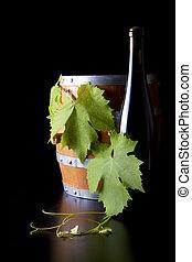 Wine bottles, barrels and grape leaf, black background. -...