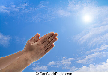 Praying hands against blue sky with clouds