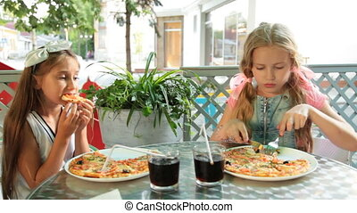 Eating Pizza in Restaurant - Two little girls eating pizza...