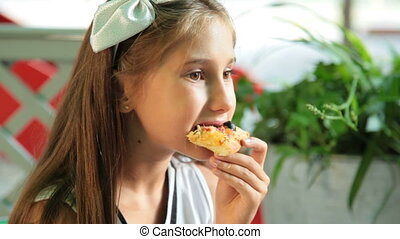 Little Girl Eats Pizza - Little girl eating pizza in a fast...