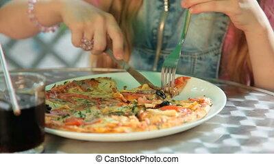 Girl Eating Pizza - Little girl eating pizza in restaurant