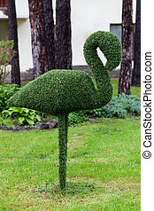 Figure flamingos made of synthetic mimics trimmed bush