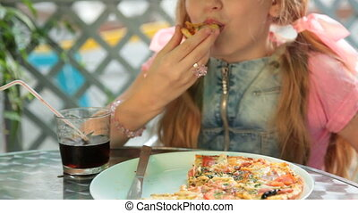 Girl Eating Pizza - Blonde girl eating pizza in a fast food...