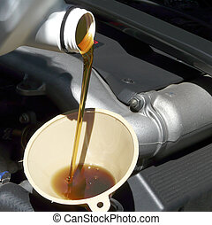 Adding Oil to Car Closeup - Oil is being added with a funnel...