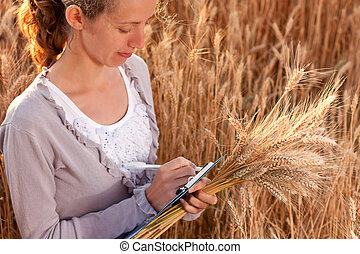 Woman agronomist writes results of his experiment in the...