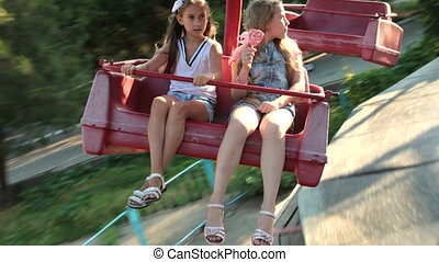 Children in the Amusement Park - Two ten-year girls on the...