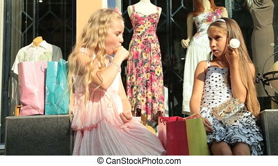 Shopping Tour - Little girls with shopping bags near the...