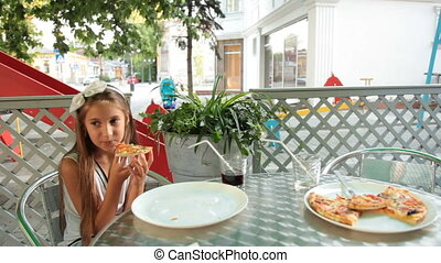 Pizza in Fast Food - Little girl eating pizza in a fast food...