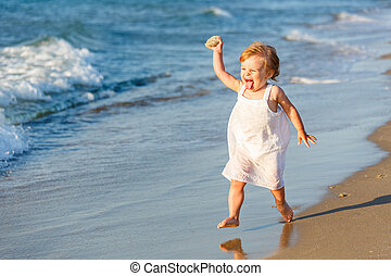 Little girl playing on the beach - Little girl in white...