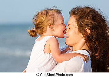 Mother and daughter on the beach - Little daughter kissing...