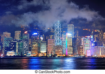 Hong Kong skyline at night with clouds over Victoria Harbour...