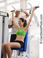 Personal trainer helping woman training in wellness club -...