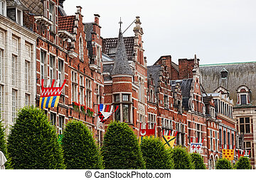 Bright flags on a wall of an ancient building, Leuven,...