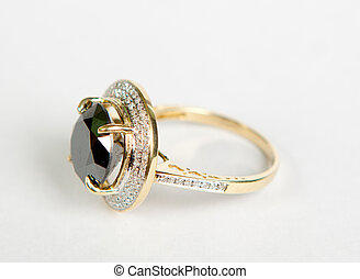 Golden ring with emeralds on a white background