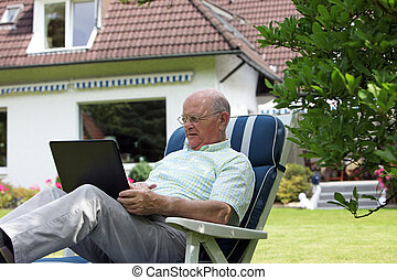 Retired man working outdoors on a laptop