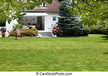 Small house with beautiful garden and a large green lawn