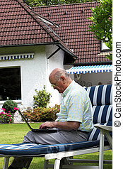 Elderly man typing outdoors on a laptop