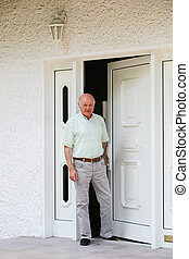 Retired man in the doorway of his home - Contented happy...
