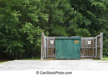 A large green metal trsh bin (dumpster) inside of a wooden...