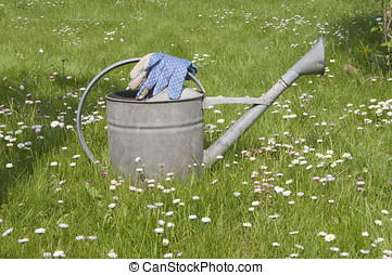 Blue garden gloves on watering can