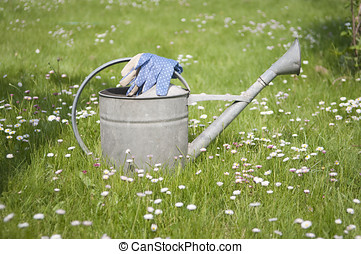 Blue garden gloves on metal watering can