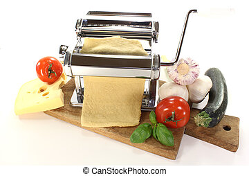 Self-made pasta - Noodle dough in a pasta machine with...