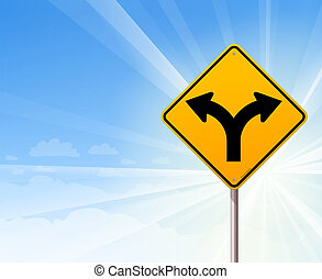 Fork in the road on blue sky - Yellow roadsign of forked...