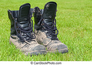 Two firm black leather boots covered in mud - Two firm black...