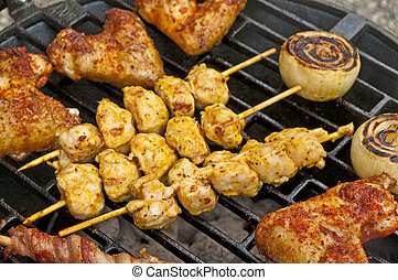 barbecue with chicken wings, meat skewer and ham