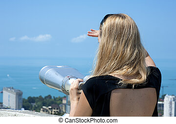 Woman on vacation looking through binoculars at the seascape