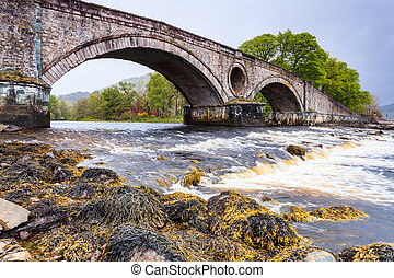 Bridge over a fast floating river - Ancient bridge over a...