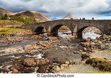 People standing on a bridge over a river with mountains in...