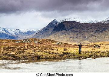 Fly fishing in a river with snow covered mountains in the...