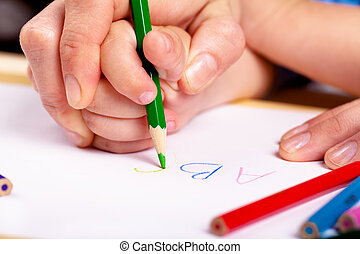 Learn to write - Child hand with pencil and woman hand...