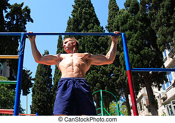 Workout - Young strong teenage athlete doing pull-up on...