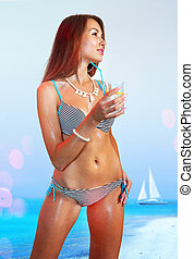 woman in bathing suit with cocktail on beach