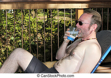 Shirtless Man Drinking Water - Man in his forties without a...